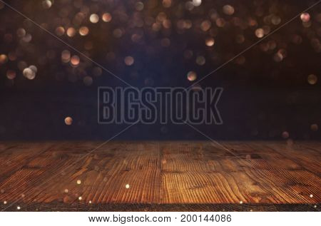 Abstract golden bokeh background in blue darkness with empty wooden table for a festive decoration
