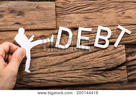 Hand Holding A Paper Cut Out Figure Kicking The Debt Word On Wooden Table