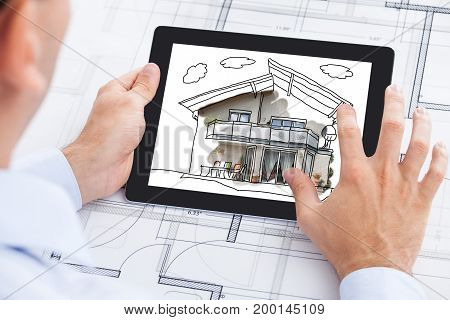 Cropped image of male architect touching house on digital tablet's screen over blueprint