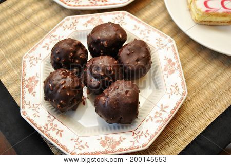 Chocolate Covered Cream Puffs with Nuts Served on a Plate