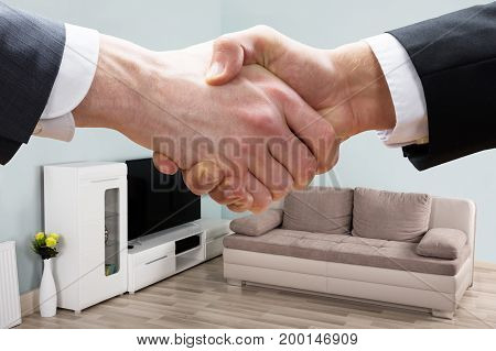 Cropped closeup of realtor shaking hands with businessman in living room