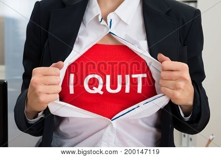 Midsection of businesswoman tearing off shirt with I Quit sign