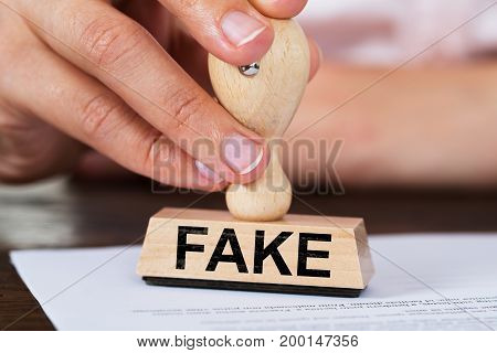 Closeup of businesswoman stamping fake rubber stamp on document at table