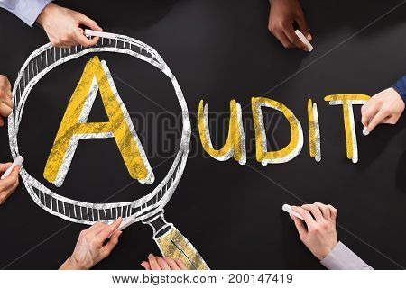 People Drawing Audit And Fraud Investigation Concept On Blackboard
