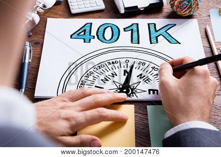 Man Writing 401k Pension Plan In Notepad On Desk