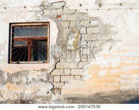 Old Wall With Cracks And Scratches. Window With Rusty Metal Bars On The Crumbling Wall Of The House.