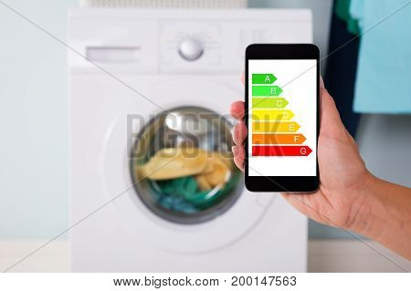 Closeup of man's hand using energy label on mobile phone against washing machine at home