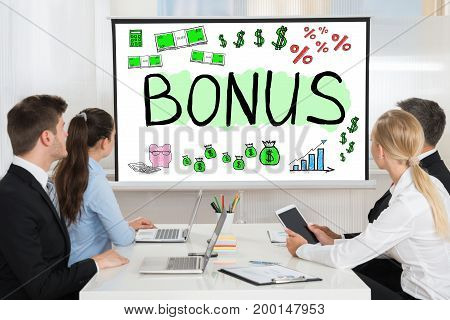 Team Looking At Bonus And Employee Compensation Presentation