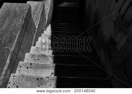 Old stone stairs going down over creepy underground grunge black and white shot.
