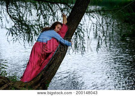 Slim sporty girl sitting in splits, Monkey yoga pose, asana Hanumanasana on tree in sunny day near lake, stretching practice
