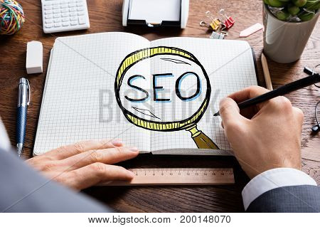 Man Drawing SEO Search Engine Optimization In Notepad