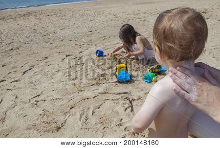 Mother applying sun cream to her baby while her daughter play on sand Huelva Spain