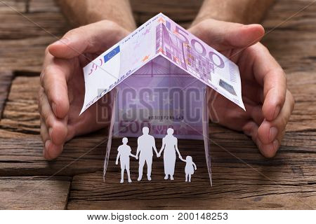 Businessman's hands covering paper family under house made from 500 euro papernotes on wooden table