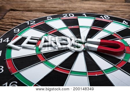 High angle view of magnet pulling leads paper text on dartboard