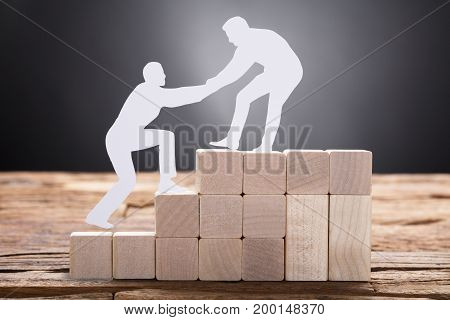 Closeup of paper businessman pulling colleague while standing on wooden blocks against black background