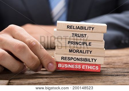Cropped image of businessman holding red business ethics block under wooden tower at table