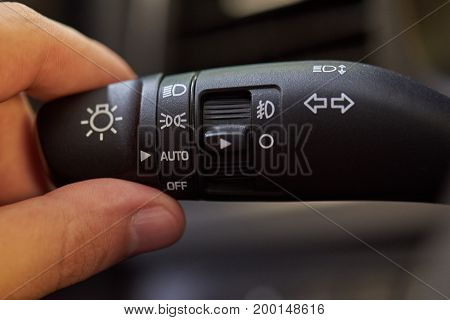 Car turn light switch handle close-up. Hand switching car light
