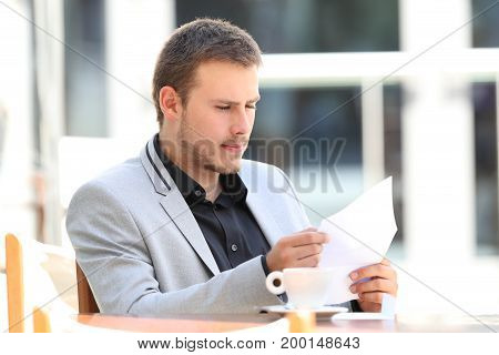 Serious executive reading a letter sitting in a coffee shop