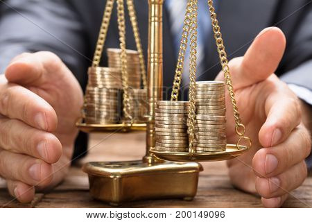 Businessman covering stacked coins on golden weighing scale at wooden table