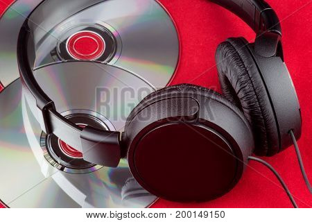 Compact discs and headphones on a red cloth surface