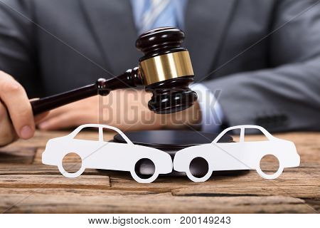 Midsection of judge hitting mallet by paper cars on wooden table