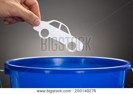 Cropped hand of businessman throwing paper car in blue bucket against gray background