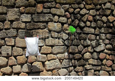 A stone wall with green broom and white pillowcase handling on the rope in Porto, Portugal