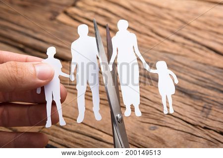 Cropped image of hand cutting paper family with scissors over wooden table