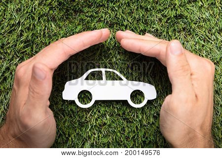 Directly above shot of businessman's hands covering paper car on grass