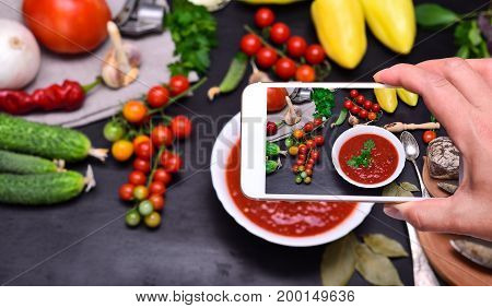 Female hand with smartphone in hand photographs soup gazpacho from red tomato in white round plate top view