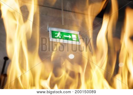 Low angle view of fire against emergency exit sign in building