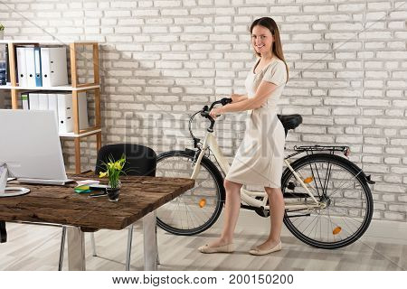 Happy Young Woman With Bicycle In Modern Office