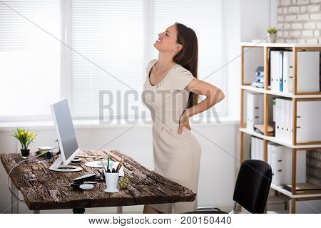 Side View Of A Young Businesswoman Suffering From Back Pain