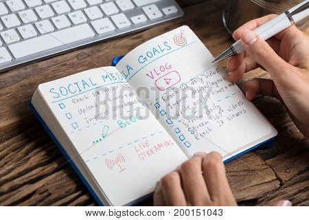 Close-up Of A Human Hand Making Social Media Plans On Notebook