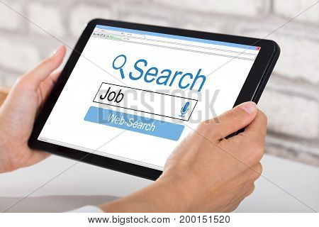 Close-up Of A Woman Searching Online Job On Digital Tablet