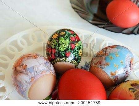 Beautifully decorated eggs by Easter holiday on a dish
