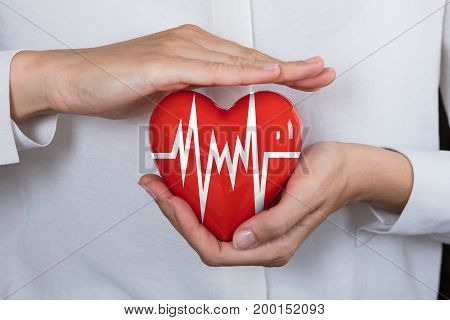 Close-up Of A Person Protecting Heart With Pulse Chart In Palm