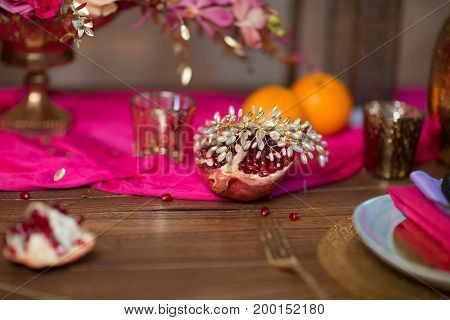 A table set vase with flowers, plates and garnet decorate in purple and pink colors