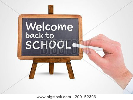 Digital composite of Hand writing Welcome back to school text on blackboard