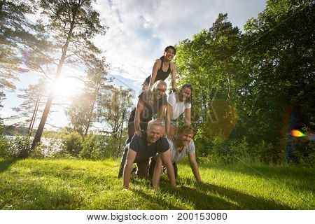 Portrait Of Happy Friends Making Human Pyramid On Field