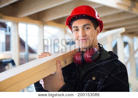 Carpenter Carrying Wood On Shoulder At Construction Site