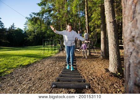 Confident Young Woman Crossing Log Bridge In Forest