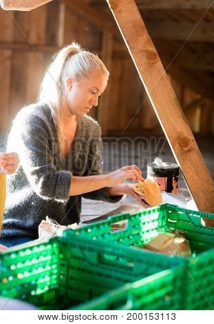 Woman Stuffing Bread While Preparing Meal In Shed