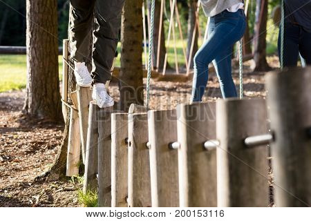 Man And Woman Crossing Log Bridge In Forest