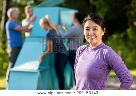 Mature Woman Smiling While Friends Making Pyramid Of Planks