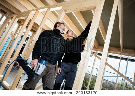 Professional Carpenters Analyzing Wood At Site