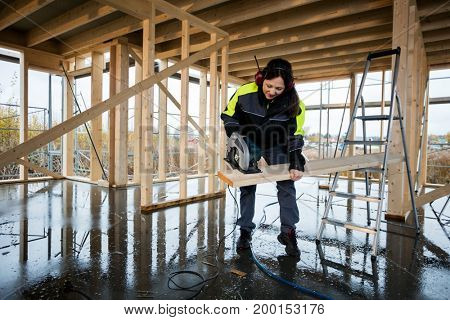 Female Carpenter Cutting Wood With Electric Saw At Construction