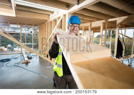 Portrait Of Confident Mature Carpenter Carrying Wood