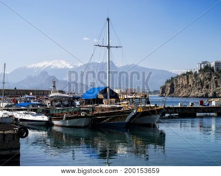 boats and silhouetted people in Antalya harbor over sunny sky