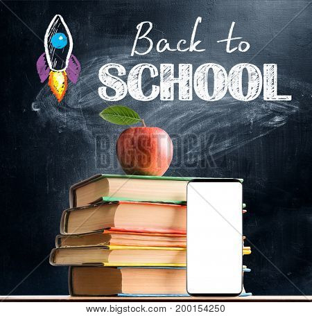 Back to School. Smartphone, books and fresh apple against blackboard